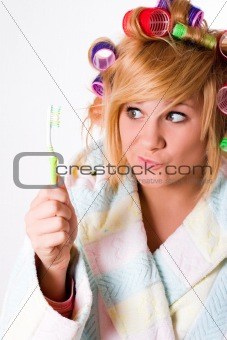 housewife with curlers and toothbrush