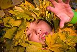 woman covered by autumnal leaves