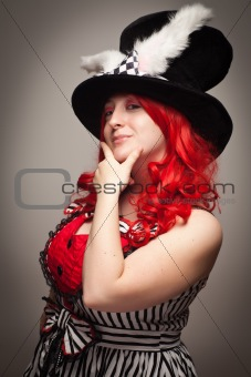 Attractive Red Haired Woman Wearing Bunny Ear Hat on a Grey Background.