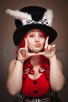 Attractive Red Haired Woman Wearing Bunny Ear Hat and Framing Her Face with her Hands on a Grey Background.