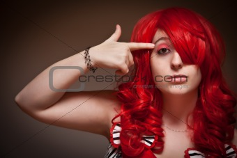 Portrait of an Attractive Red Haired Woman with Hand in the Shape of a Gun to Her Head on a Grey Background.