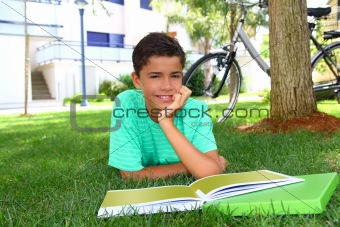 boy teenager studying laying green grass garden