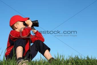 Boy looks into binoculars