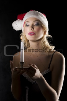 santa claus in dark blowing on candle