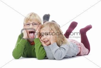 portrait of two young siblings looking at camera, making faces- isolated on white