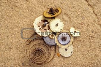 part of clockwork mechanism on the sand