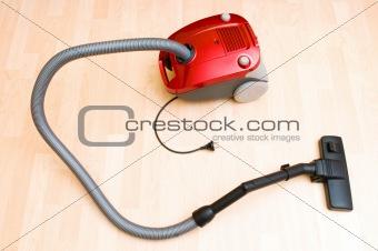 Vacuum cleaner on the wooden floor