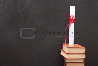 Chalkboard with a diploma and books
