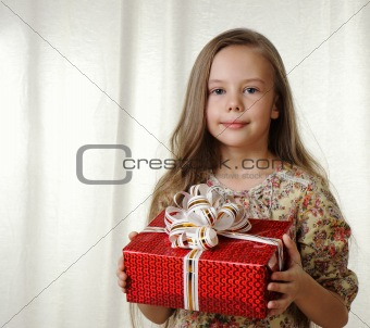 Little girl holds a red box with a gift
