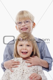 portrait of two young siblings looking at camera, smiling - isolated on white