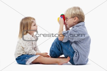 siblings taking pictures of each other with toy camera - isolated on white