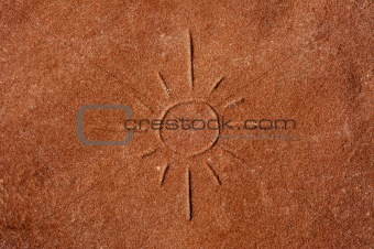 a sun carved on a red stone