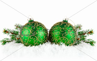 green balls on snow with branch firtree