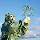 Man in chemical suit and gas mask with plant in hands