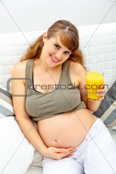 Smiling beautiful pregnant woman sitting on sofa with glass of juice  in hand