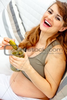 Laughing beautiful pregnant female sitting on sofa and  holding jar of pickles in hands
