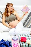 Happy  beautiful pregnant woman sitting on sofa with gifts for her unborn baby