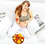 Smiling  beautiful pregnant female sitting  on sofa and  holding fruit in hand