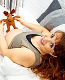 Happy beautiful pregnant woman lying on sofa and holding toy. Close-up.