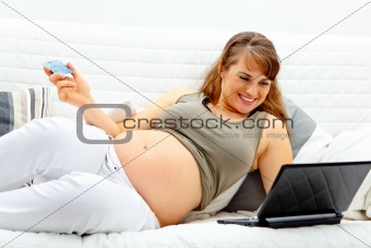 Smiling beautiful pregnant woman using credit card to shop from  internet
