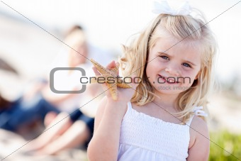 Adorable Little Blonde Girl with Starfish at The Beach.