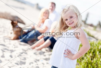 Adorable Little Blonde Girl Having Fun At the Beach with Her Family.