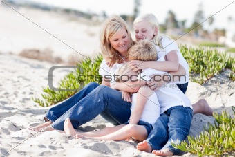 Attractive Mom Having Fun with Her Cute Children at The Beach.