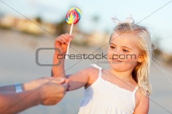 Adorable Little Girl Picking out Lollipop from Mom at the Beach.