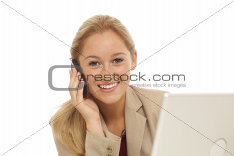 Portrait of young business girl using cell phone at desk with laptop