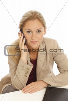 Portrait of young business girl sitting at desk with cell phone