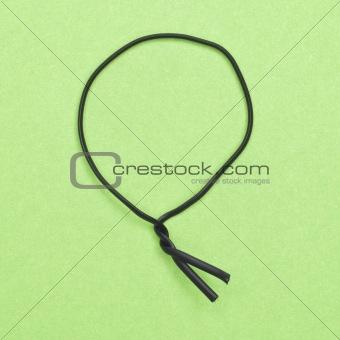 Black Twist Tie on a Green Background.