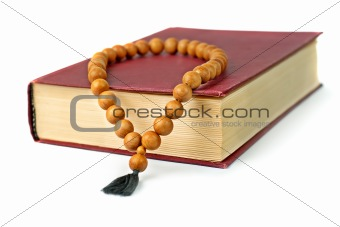 Old book with a claret  cover and wooden rosary.