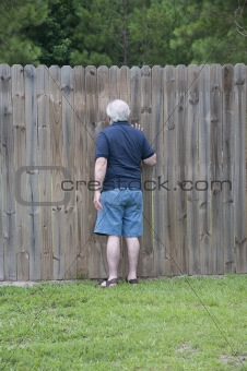 Adult Man Peeking Through a Hole in the Fence