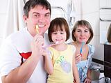 Mom, daughter and father brush their teeth