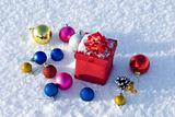 Red gift box on snow with christmas balls