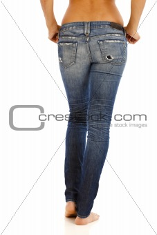 Back side of young woman with bare top wearing worn jeans