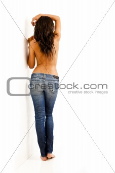 Back view of young woman with bare top wearing worn jeans
