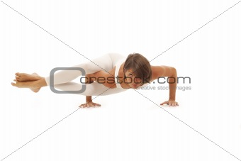 Young woman doing yoga Side Crow Pose