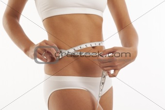 Young woman in underwear with measuring tape