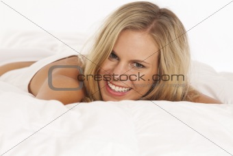 Portrait of young woman laying in bed