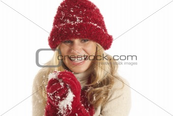 Portrait of young woman with red hat and gloves making snowball