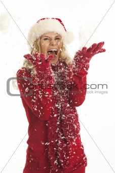 Young woman with Santa hat throwing snow