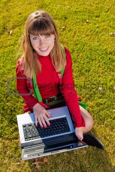 Beautiful girl with a laptop on the grass