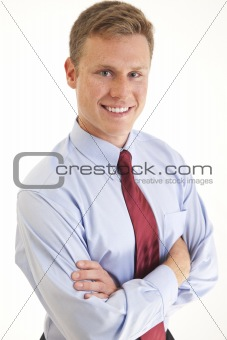 Portrait of smiling young businessman with arms folded