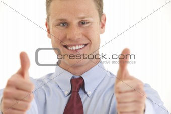 Portrait of smiling young businessman with two thumbs up