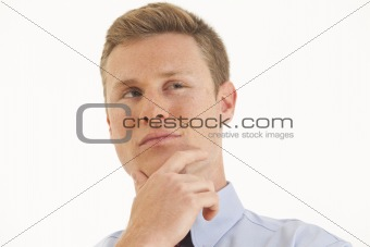 Portrait of young businessman thinking with hand on chin