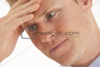 Portrait of stressed young businessman with hand on forehead