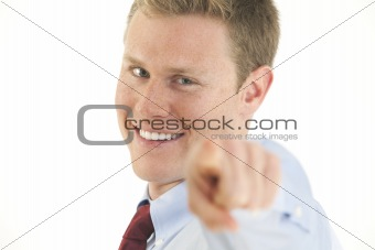 Portrait of smiling young businessman pointing finger at camera