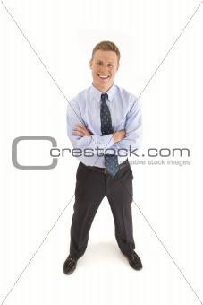 Portrait of smiling young businessman standing  with arms crossed