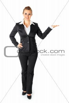 Full length  portrait  of smiling modern business female presenting something on empty hand